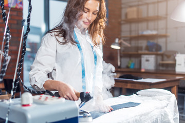 Fashion designer using steam iron to press cloth working in studio