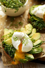 Sandwich with avocado and poached egg with addition of fresh herbs