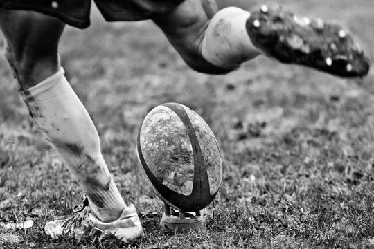 Legs of rugbyplayer kicking ball