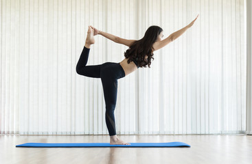 Young Asian woman practicing yoga. Copy space. Happiness, smiling.