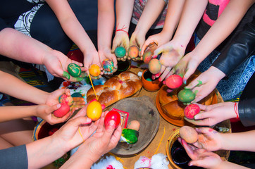 Children decorate Easter eggs with paints made from natural materials.
