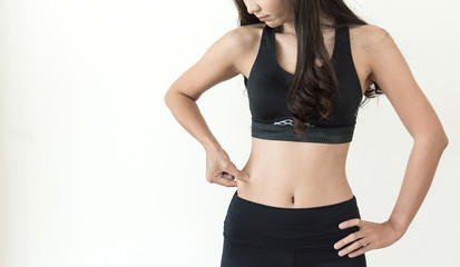 Young Asian woman pinched her belly on white isolated background. Slim girl with copy space.