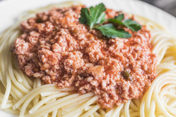 Spaghetti with meat sauce on white plate close up