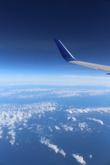 An airplane's wing over a blue and cloudy sky