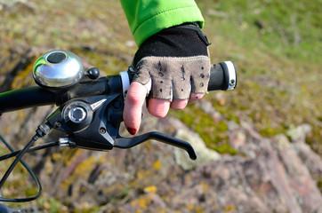 Female hand in a glove on the handlebars of a mountain bike
