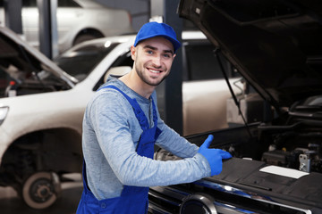 Young mechanic standing in front of open car hood