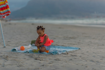 Little girl having snacks at the beach