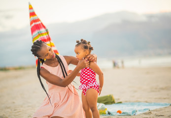 Beautiful mother caring for little girl at the beach
