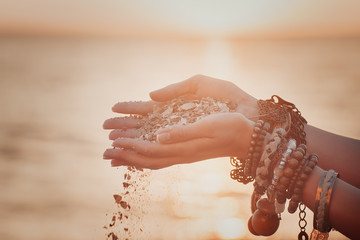 A woman with sand falling through her hands.summer background