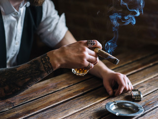 A young man smoking a cigar in a pub