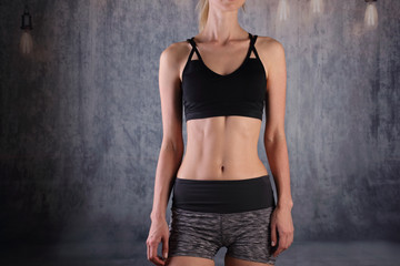 Sport, fit woman. Fit Female body with perfect abdomen muscles on grey background. Dieting, fitness, active lifestyle concept,
