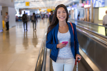 Travel woman using smartphone at airport. Young asian traveler holding mobile phone app in terminal or train station. Tourist businesswoman on commute or vacation.