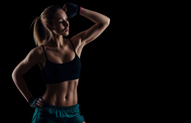 Sporty young girl in sportswear showing muscles on black background. Tanned young athletic woman. A great sport female body.