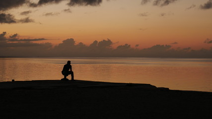 Solitary at Sunset A man watches the setting sun in the Northern Mariana Islands.