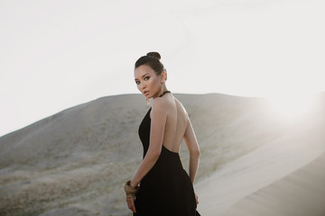 Woman in a black dress on a dune of desert