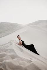 Beautiful sexy asian woman on a dune of desert