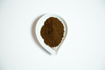 Ground Puerto Rican coffee in a white teardrop tray