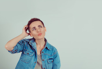 Closeup portrait young woman short hair scratching head, thinking daydreaming something looking up isolated green grey wall background. Human facial expression emotion feeling body language perception