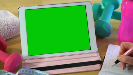 Tablet PC with green screen with exercise equipment