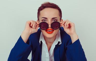 Slightly surprised woman holding sunglasses