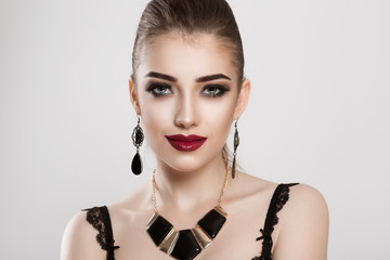 Beauty Fashion Model Girl with smokey eyes makeup burgundy red lips black jewelry new trend earrings pendant looking at you camera light smile isolated white grey background