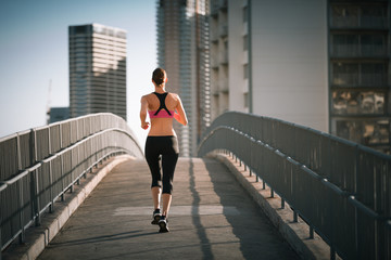 Female runner running on city bridge.