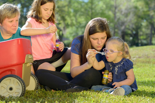 child with down syndrome blowing bubbles with sisters