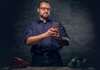 A man using a smart phone in a room with analog cell phones.