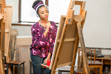 Young creative african ethnicity student drawing on the easel at the university studio
