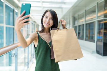 Happy woman holding shopping bag and taking selfie