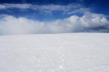 следы на белом снеге уходят за горизонт в облако