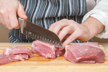 Chef's hands with a knife cuts the meat on the wooden board in the kitchen. Cooking at restaurant. Healthy eating and lifestyle.