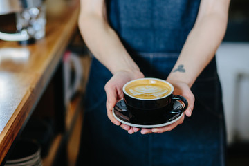 female barista holding cup of cappuccino. Close up.