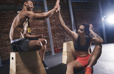 Sporty couple high five at gym