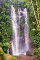 Tropical traveling. Young woman in hat with rucksack enjoying waterfall view.