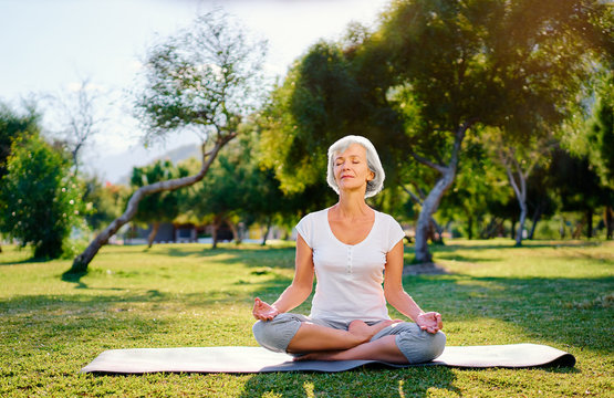 Yoga at park. Middle age woman in lotus pose sitting on green grass. Concept of calm and meditation.