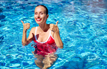 Happy summer vacation. Smiling young woman in red swimsuit showing thumbs up at swimming pool.