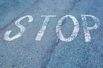 Word Stop written on an asphalt road, Top view on the road in perspective.