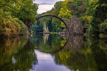 Autumn, cloudy evening over Devil's bridge in the park Kromlau, Germany