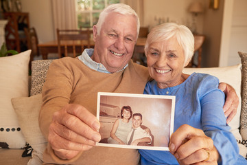Smiling senior couple holding a photo of their youthful selves