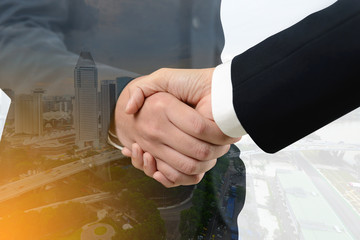 Double exposure of handshake between businessman with cityscape - Business concept, Immovable property concep