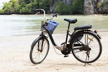 Vintage bicycle on white sand beach over blue sea