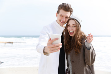 Happy young couple taking selfie with cell phone outdoors