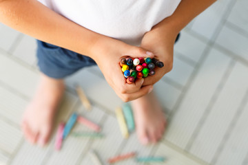 child's hands with lots of colorful wax crayons