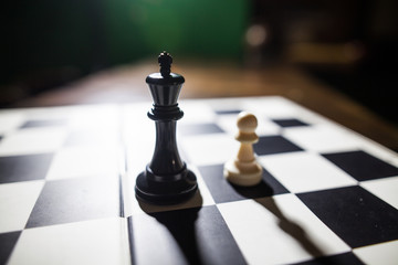 Black king and white pawn on chess board