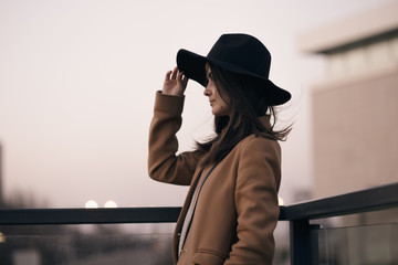 Portrait of woman in hat at city background