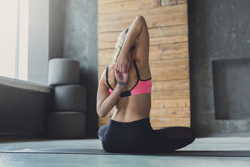 Woman stretching hands behind back at yoga class