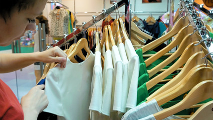 A female customer is browsing through the cloths. Video shows a female contemplating in which shirt to pick. Variety of sizes and color are offered.