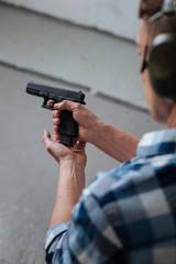 Brutal professional marksman reloading his gun