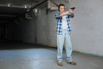 Strong well built man visiting a shooting gallery